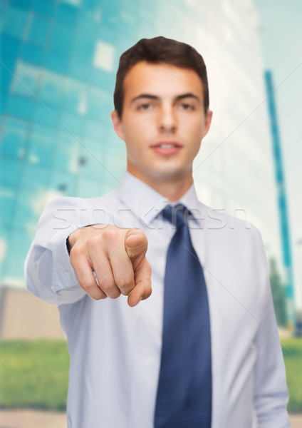 friendly young buisnessman pointing finger Stock photo © dolgachov