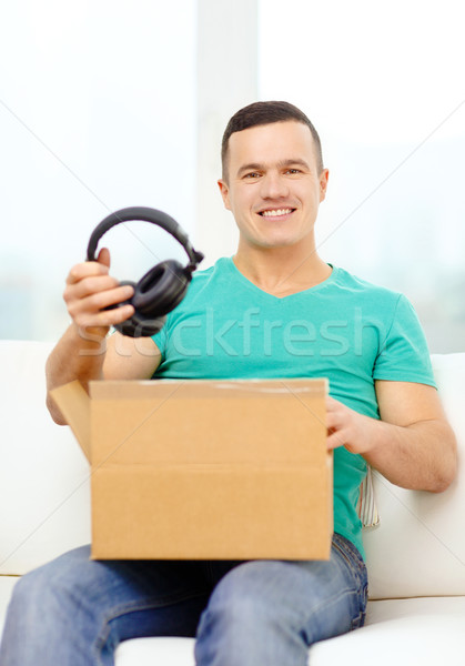 opening cardboard box and taking out headphones Stock photo © dolgachov