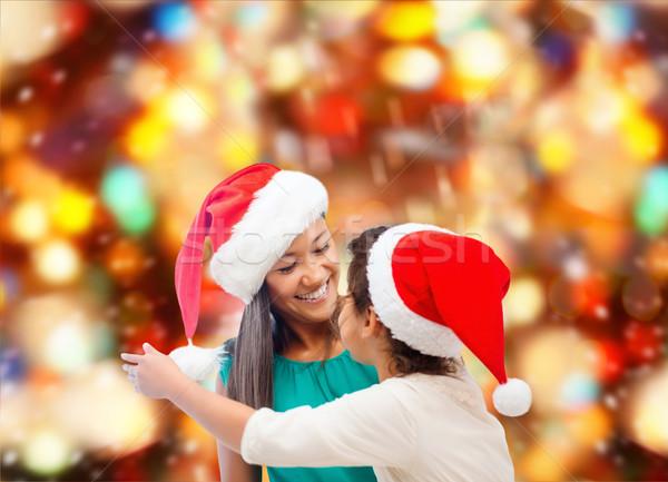 happy mother and girl in santa hats Stock photo © dolgachov