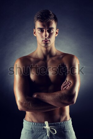 young man on fighting stand over black background Stock photo © dolgachov