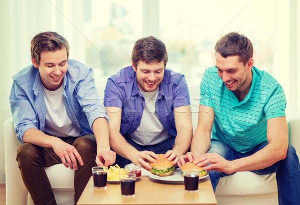 smiling friends with soda and hamburgers at home Stock photo © dolgachov