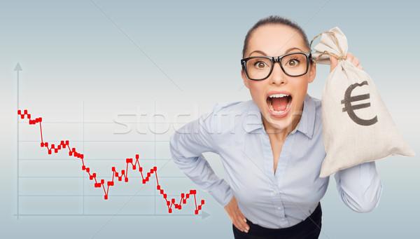 shocked businesswoman holding money bag with euro Stock photo © dolgachov