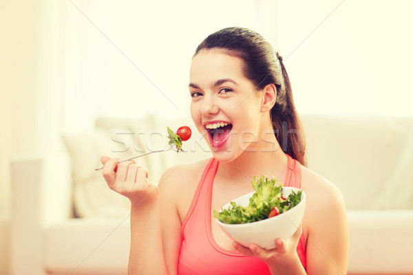 smiling teenage girl with green salad at home Stock photo © dolgachov