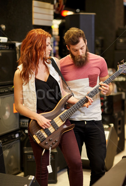 musicians playing bass guitar at music store Stock photo © dolgachov