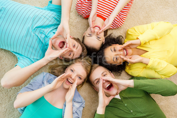 Stock photo: smiling people lying down on floor and screaming