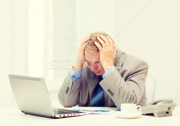 upset older businessman with laptop and telephone Stock photo © dolgachov