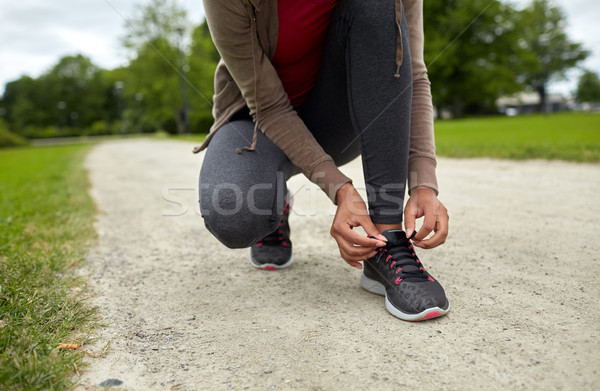 Stock photo: close up of woman tying shoelaces outdoors
