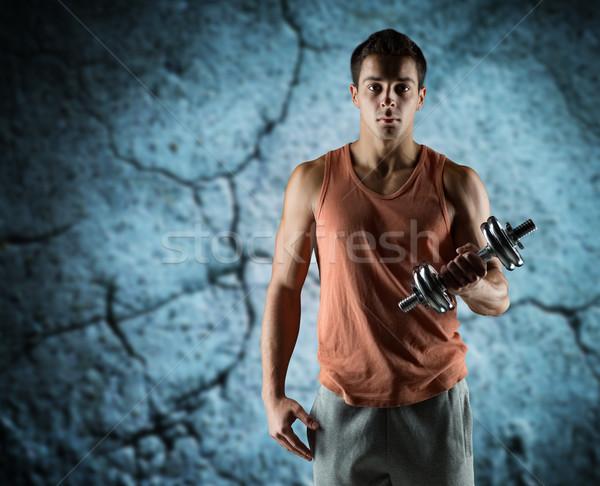 молодым человеком бицепс спорт фитнес тяжелая атлетика Сток-фото © dolgachov