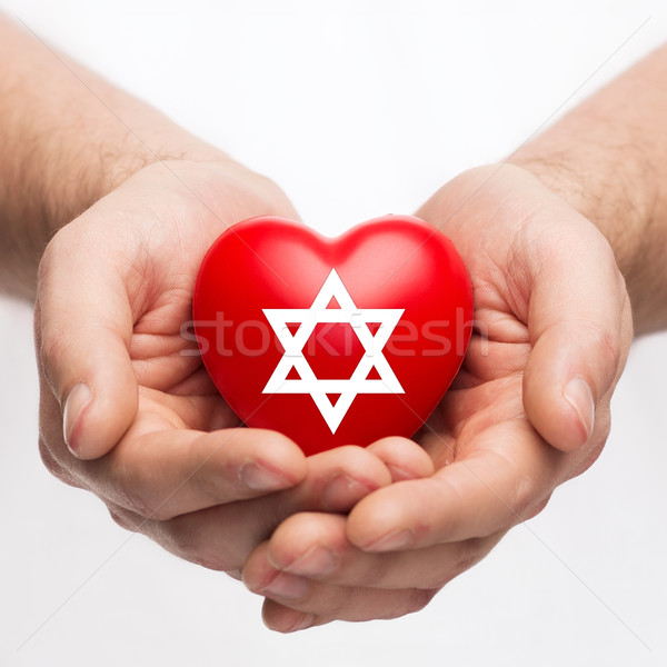 male hands holding heart with star of david Stock photo © dolgachov