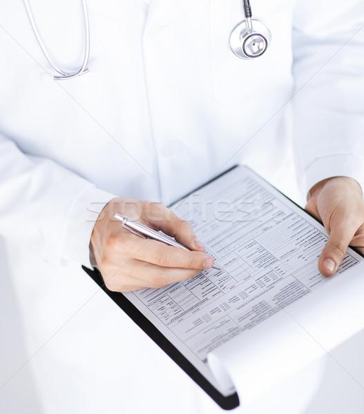 male doctor holding prescription paper in hand Stock photo © dolgachov