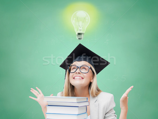 happy student girl in bachelor cap with books Stock photo © dolgachov