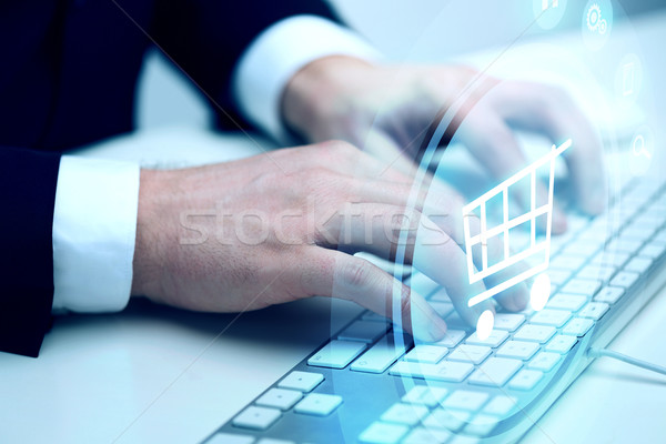 close up of hands with  keyboard and shopping cart Stock photo © dolgachov