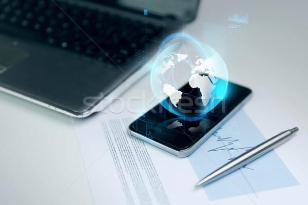 Közelkép okostelefon Föld földgömb hologram üzlet Stock fotó © dolgachov