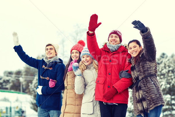 happy friends waving hands on ice rink outdoors Stock photo © dolgachov