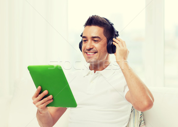 smiling man with tablet pc and headphones at home Stock photo © dolgachov