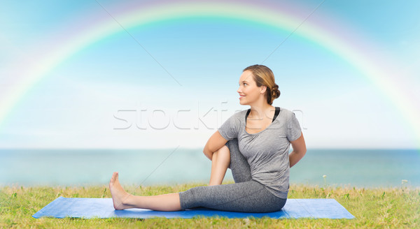 woman making yoga in twist pose on mat Stock photo © dolgachov
