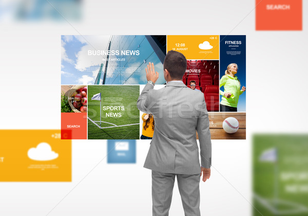 businessman with virtual projection of news pages Stock photo © dolgachov