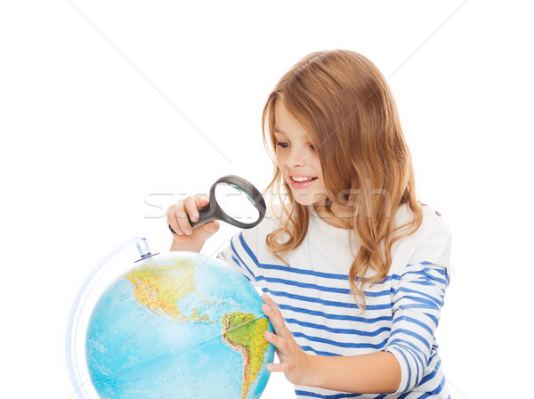 student girl looking at globe with magnifier Stock photo © dolgachov