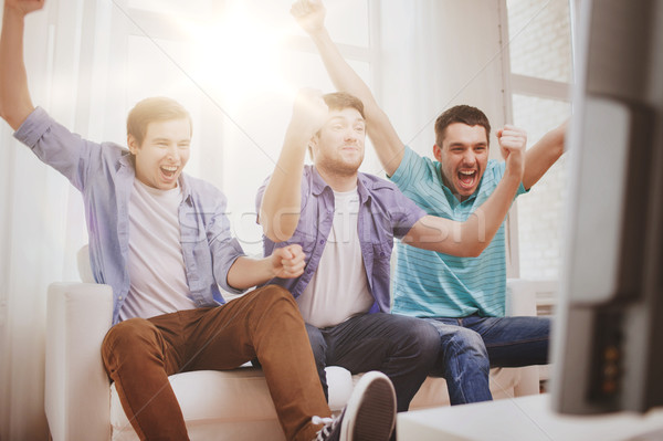 happy male friends at home Stock photo © dolgachov