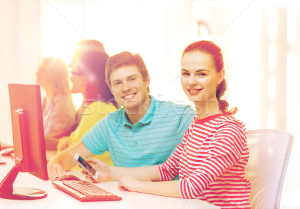 smiling student with smartphone in computer class Stock photo © dolgachov