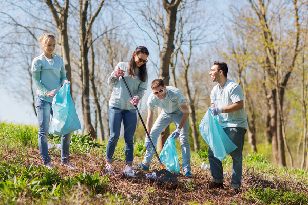 Stock photo: volunteers with garbage bags cleaning park area