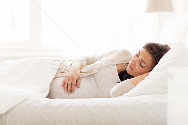 happy pregnant woman sleeping in bed at home Stock photo © dolgachov