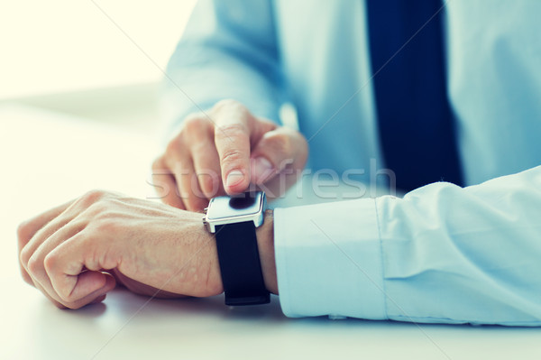 close up of male hands setting smart watch Stock photo © dolgachov