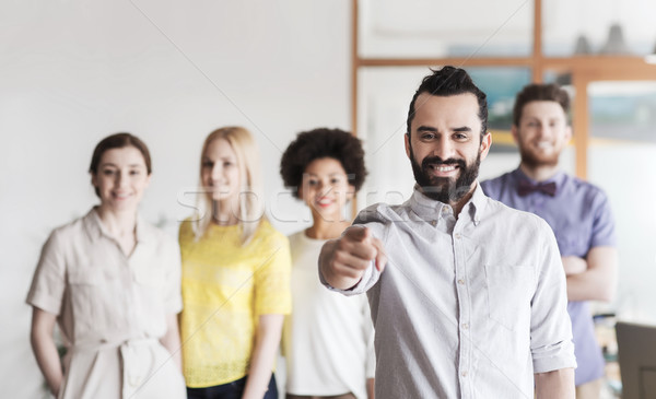 Stock photo: happy man pointing finger at you over office team