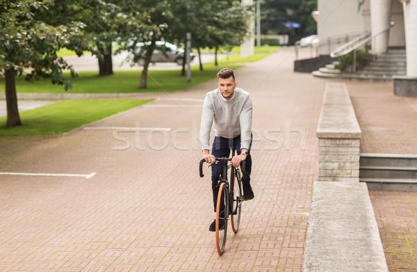 young man riding bicycle on city street Stock photo © dolgachov