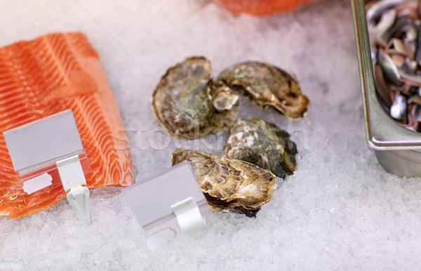 salmon fish and oysters on ice at grocery stall Stock photo © dolgachov