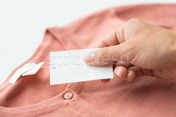 close up of hand with price tag and clothing item Stock photo © dolgachov