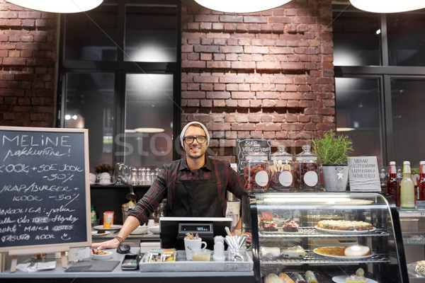 happy seller man or barman at cafe counter Stock photo © dolgachov