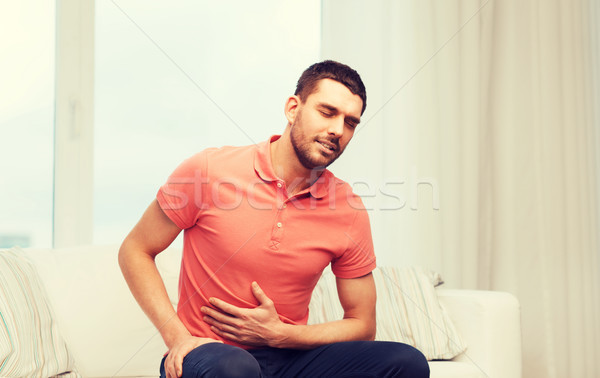 Infeliz homem sofrimento dor de estômago casa pessoas Foto stock © dolgachov