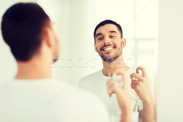 man with perfume looking to mirror at bathroom Stock photo © dolgachov