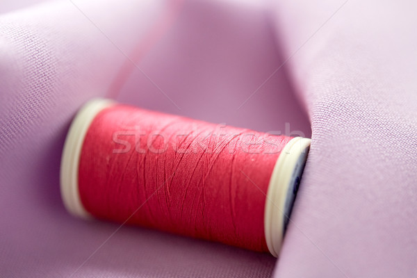 red thread spool on cloth Stock photo © dolgachov