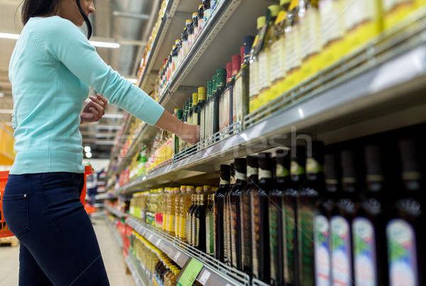 woman choosing olive oil at supermarket or grocery Stock photo © dolgachov