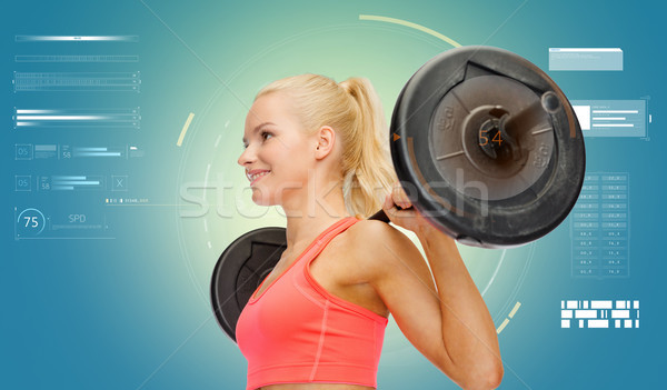 Jeune femme muscles barbell sport fitness Photo stock © dolgachov