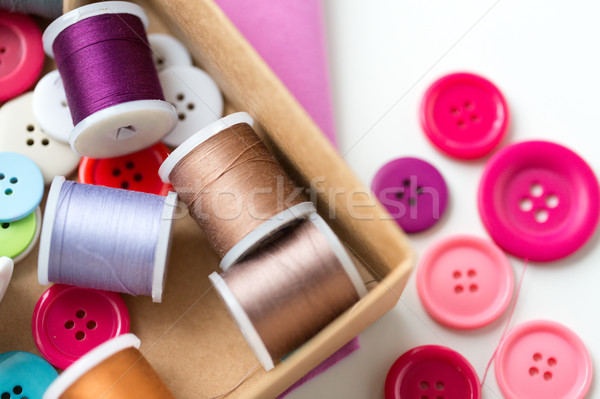 box with thread spools and sewing buttons on table Stock photo © dolgachov