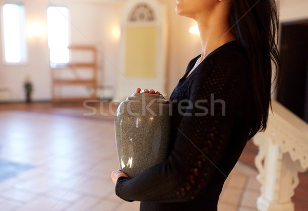 Stock photo: close up of woman with cremation urn in church