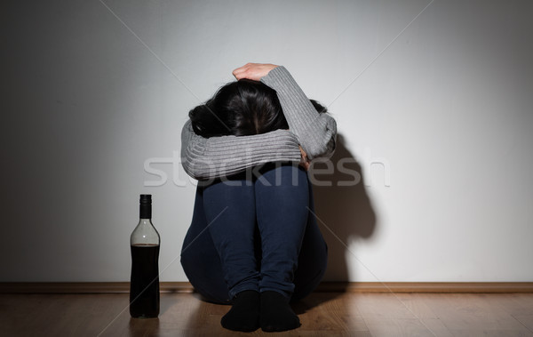 woman with bottle of alcohol crying at home Stock photo © dolgachov