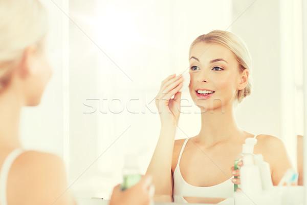 Jonge vrouw lotion wassen gezicht badkamer schoonheid Stockfoto © dolgachov