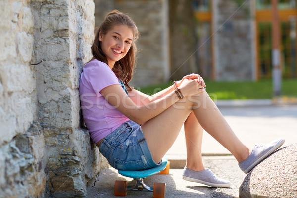 happy teenage girl sitting on longboard on street Stock photo © dolgachov