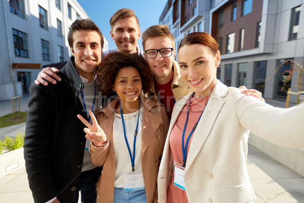 team with conference badges taking selfie in city Stock photo © dolgachov