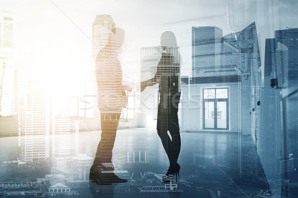 business people shaking hands over city background Stock photo © dolgachov