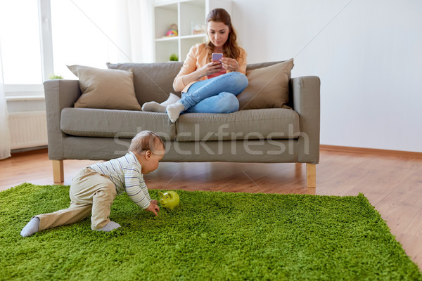 mother with smartphone and baby playing at home Stock photo © dolgachov