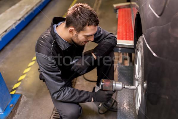 auto mechanic with screwdriver changing car tire Stock photo © dolgachov