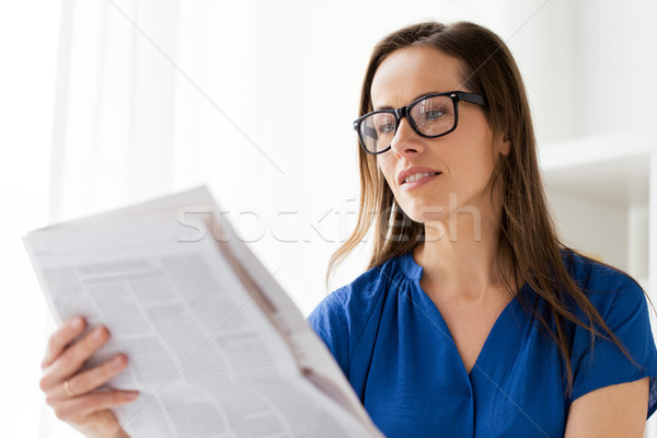 happy woman in glasses reading newspaper at office Stock photo © dolgachov