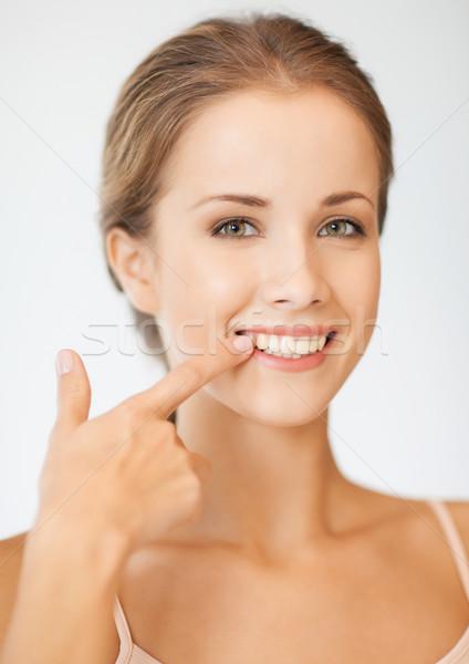 Piękna kobieta wskazując zęby zdjęcie kobieta strony Zdjęcia stock © dolgachov
