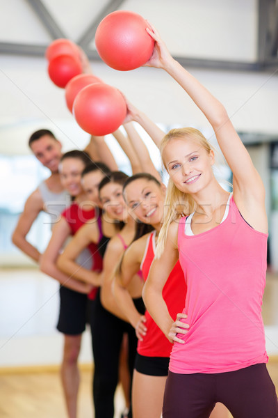 group of smiling people working out with ball Stock photo © dolgachov