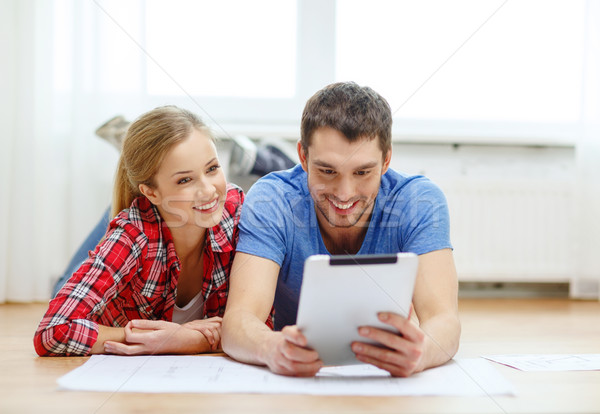 Stock photo: smiling couple looking at tablet pc at home